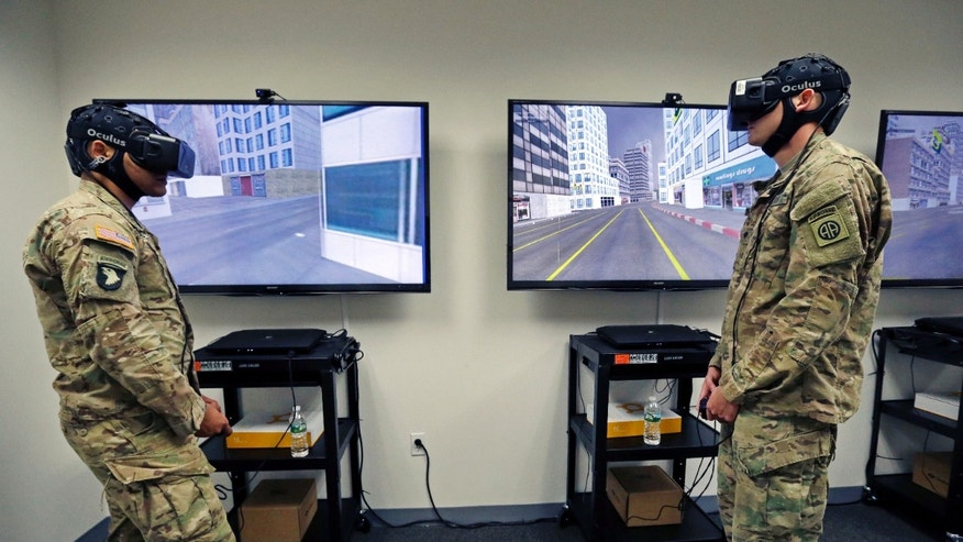 Soldiers wear virtual reality headsets as their neurological, psychological and behavioral responses are monitored during a team drill, Tuesday, Oct. 18, 2016, at the Center for Applied Brain and Cognitive Sciences in Medford, Mass. The Center was jointly founded by the Army's Natick Soldier Research, Development and Engineering Center and Tufts University's School of Engineering. (AP Photo/Elise Amendola)