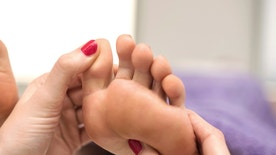 Woman having a pedicure treatment at a spa or beauty salon with the pedicurist massaging feet.
