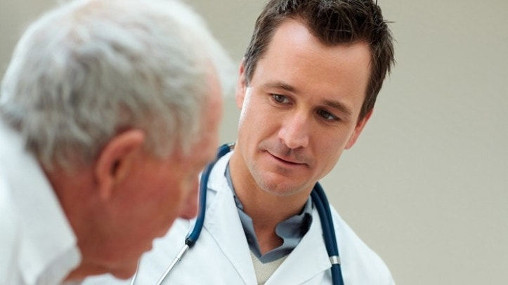 Handsome successful doctor speaking to a senior patient