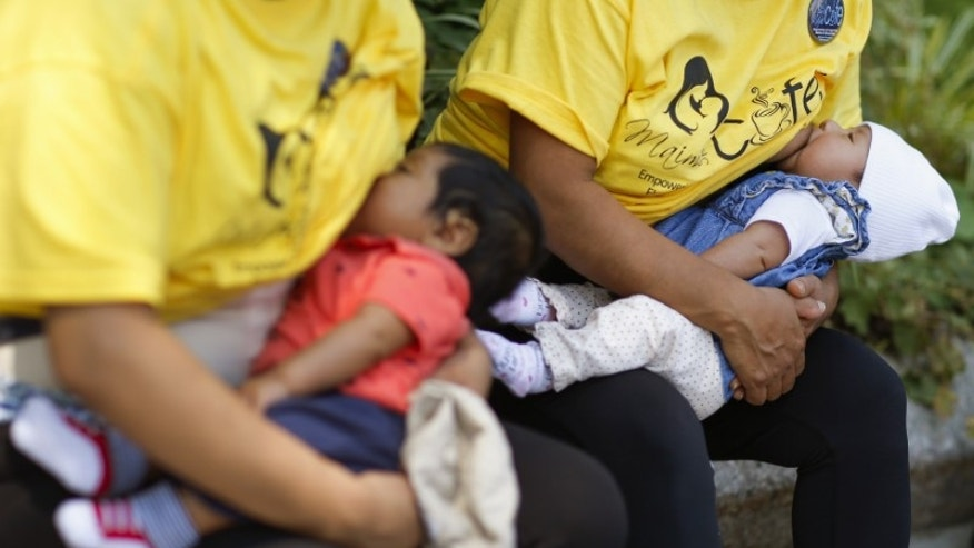Mothers breastfeed their babies while attending a rally to raise public awareness and support for breastfeeding near the steps of New York City Hall in Manhattan