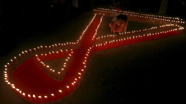 An activist from a NGO lights candles during an AIDS awareness campaign in Agartala