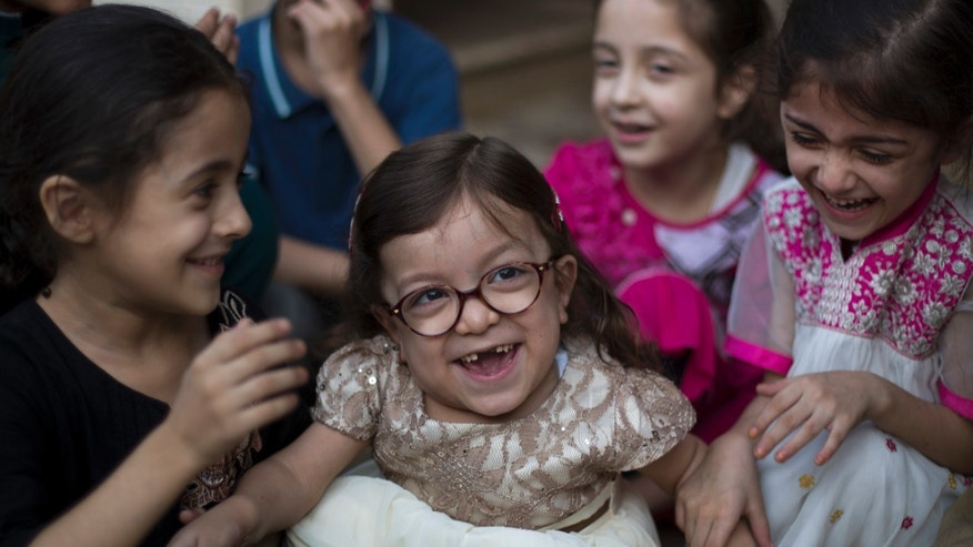 In this Thursday, Oct. 20, 2016 photo, Maria, center, who is suffering from a disease known as Morquio Syndrome, plays with family members in Rawalpindi, Pakistan. The U.S. embassy in Islamabad issued a last minute visa to Maria, an ailing 6-year-old Pakistani child, afflicted with a painful genetic disorder, and her parents who turned to the media as the date for their child's life altering operation in the United States loomed. (AP Photo/B.K. Bangash)