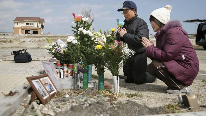 Tsutoshi Yoshida and his wife Seiko pray for their daughter who was killed by the 2011 tsunami, in Namie, Fukushima, northern Japan Friday, March 11, 2016.  Japan on Friday marked the fifth anniversary of the 2011 tsunami that killed more than 18,000 people and left a devastated coastline along the country's northeast that has still not been fully rebuild. (Hironori Asakawa/Kyodo News via AP) JAPAN OUT, MANDATORY CREDIT