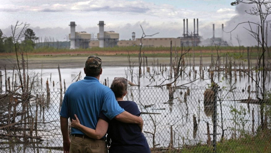 FILE - In this April 25, 2014, file photo, Bryant Gobble, left, embraces his wife, Sherry Gobble, right, as they look from their yard across an ash pond full of dead trees toward Duke Energy's Buck Steam Station in Dukeville, N.C. Duke Energy has agreed to remove millions of tons of coal ash containing toxic heavy metals from a power plant in North Carolina. The nation's largest electricity company announced Wednesday, Oct. 5, 2016  that it would dig up three huge pits of water-logged ash at the Buck Steam Station near Salisbury. The ash will be dried and either offered for use in making concrete or moved to lined landfills elsewhere.  (AP Photo/Chuck Burton, File)