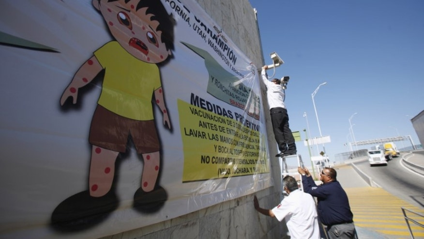 A worker places a banner for a measles prevention programme during an awareness campaign by health workers at the Ciudad Juarez Mexican border crossing with El Paso, Texas