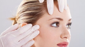 closeup of doctor conduct skin check before plastic surgery