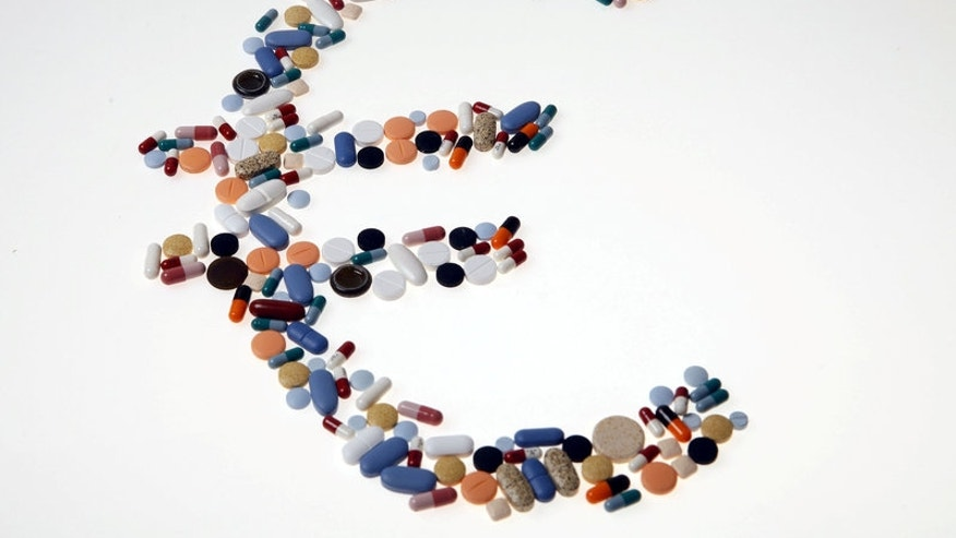 Pharmaceutical tablets and capsules are arranged on a table in this picture illustration