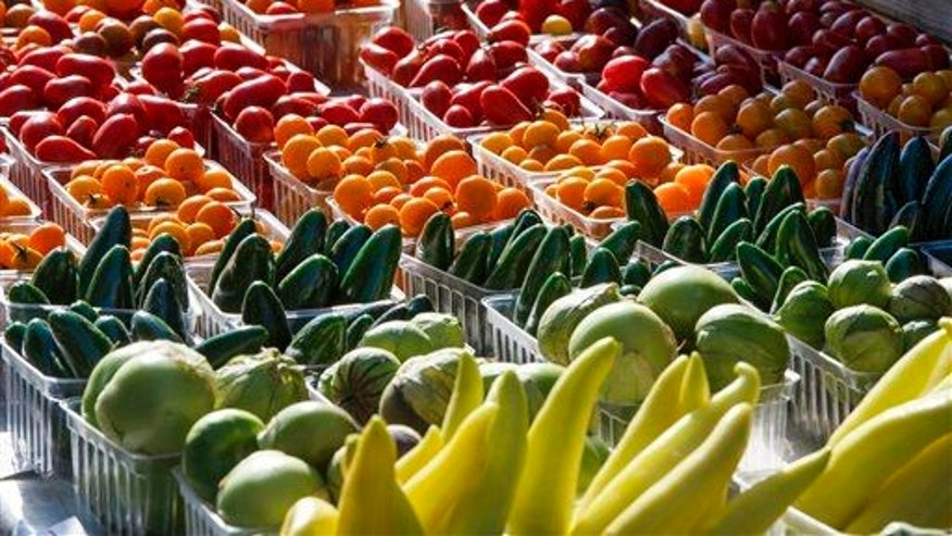 Fresh-picked tomatoes, cucumbers and other summer garden vegetables are displayed for sale at a farmers market in Falls Church, Va., Saturday, Aug. 8, 2015.