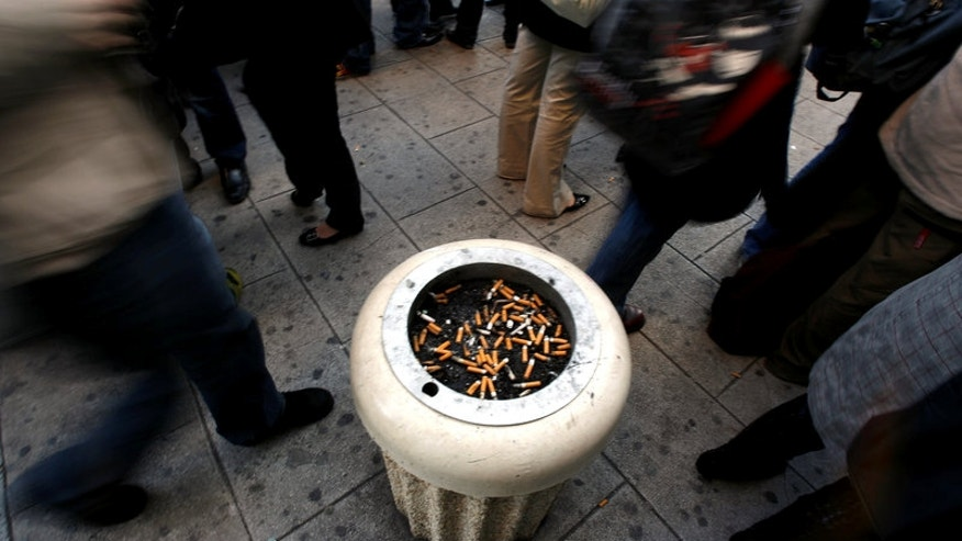 School students stand around an ashtray on the pavement outside their school in Nice