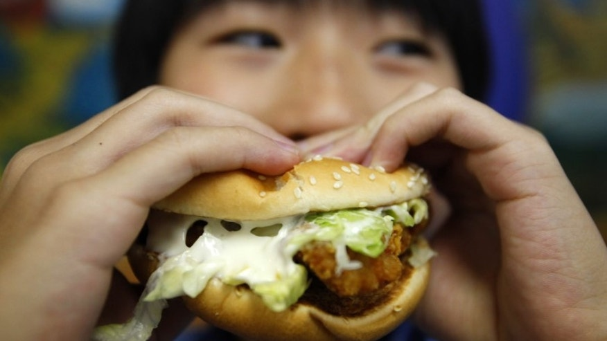 A boy poses with a chicken burger at a fast food outlet in Taipei