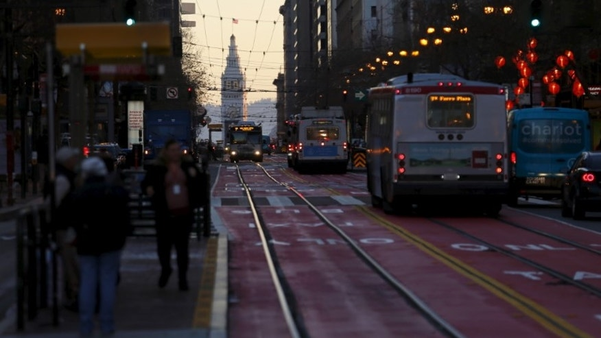City buses travel down a city street in San Francisco, California