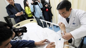 """Reporters take pictures of an """"ear"""" growing on the arm of a patient who lost his right ear in an accident, at the first affiliated hospital of Xi'an Jiaotong University, in Xi'an, Shaanxi province, China, November 9, 2016. The growing """"ear"""", which will be transplanted onto the patient's head in a following surgery, was taken from the patient's rib cartilage, cut into the shape of a ear and placed under the skin flap of the arm. China Daily/via REUTERS ATTENTION EDITORS - THIS IMAGE WAS PROVIDED BY A THIRD PARTY. EDITORIAL USE ONLY. CHINA OUT. NO COMMERCIAL OR EDITORIAL SALES IN CHINA.         - RTX2SQLH"""
