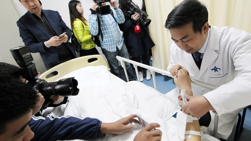 "Reporters take pictures of an ""ear"" growing on the arm of a patient who lost his right ear in an accident, at the first affiliated hospital of Xi'an Jiaotong University, in Xi'an, Shaanxi province, China, November 9, 2016. The growing ""ear"", which will be transplanted onto the patient's head in a following surgery, was taken from the patient's rib cartilage, cut into the shape of a ear and placed under the skin flap of the arm."