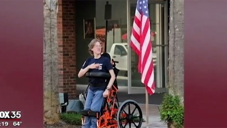 Arek Trenholm stands near an American flag with the help of his standing wheelchair.