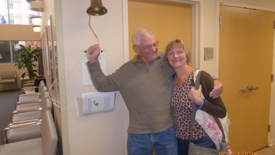 Ken Felix ringing the post-cancer treatment bell at the Cleveland Clinic with his wife of 40 years, Jan.