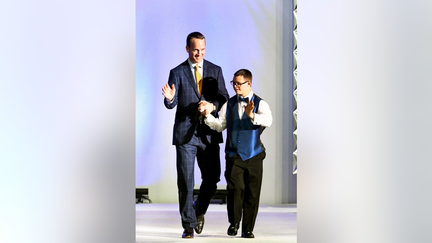 DENVER, COLORADO - NOVEMBER 12: NFL star Peyton Manning walks down the runway with one of the many models during , during the Global Down Syndrome Foundation's 2016 'Be Beautiful, Be Yourself' fashion show at the Hyatt Regency Hotel on November 12, 2016 in Denver, Colorado. A night of advocacy, and empowerment, the event is the single largest fundraiser benefitting people with Down syndrome in the world, having raised over $12 million to date.  (Photo by Helen H. Richardson/The Denver Post)