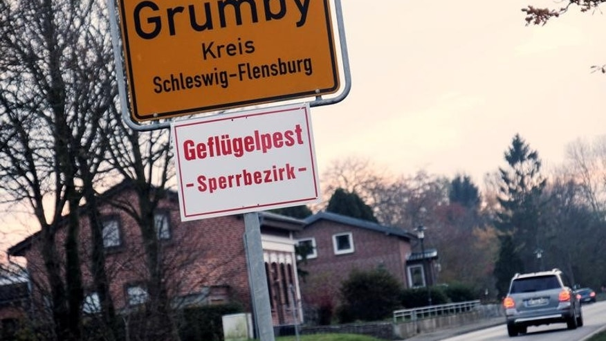 A car drives past the town sign in the northern German village of Grumby