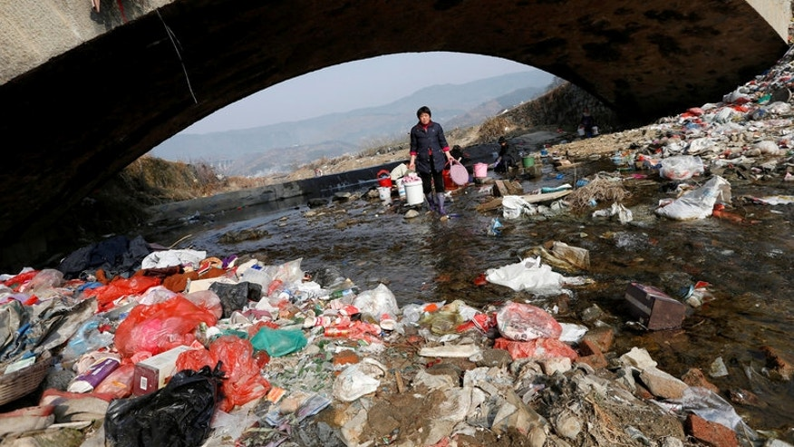Villagers wash clothes in the garbage-filled Shenling River, in Yuexi county, Anhui province