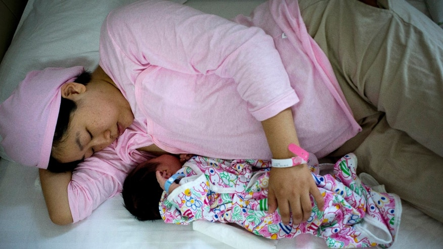 New mother Qi Wenjuan breastfeeds her 1-day-old son at Tiantan Hospital's maternity ward in Beijing, China. (AP Photo/Andy Wong)