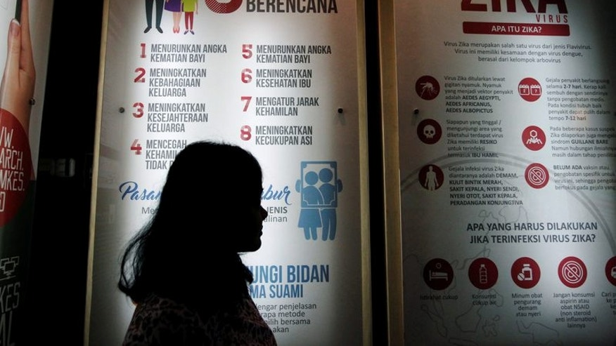 A woman stands near a poster explaining about the Zika virus at the Ministry of Health office in Jakarta