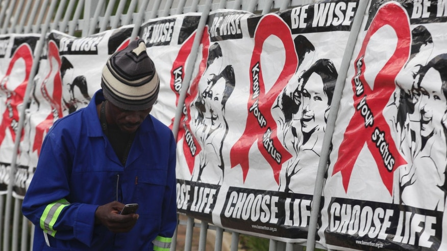 Dec. 1, 2014: In this file photo, a man makes a call on a mobile phone as he passes World AIDS Day banners on the perimeter of an office building in Sandton, Johannesburg, South Africa.