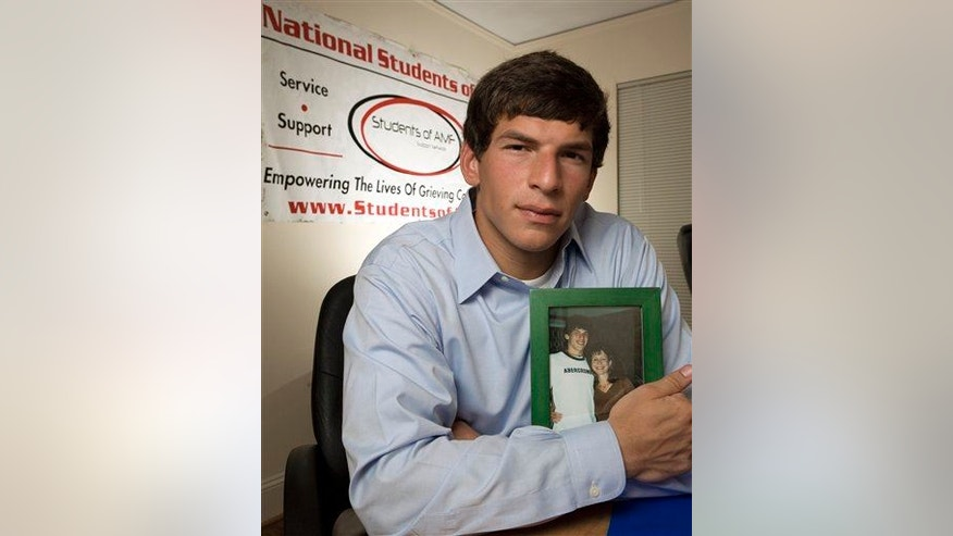 Before he became a doctor and researcher, David Fajgenbaum founded Students of Ailing Mothers and Fathers while at Georgetown after his mother died of brain cancer. He holds her photo at his home in Raleigh, NC, June 29, 2007.