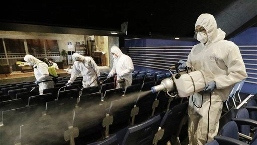 Workers wearing protective gear spray antiseptic solution as a precaution against the spread of the MERS virus at Uniplex Art Center in Seoul, South Korea, Thursday, June 17, 2015.