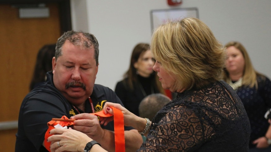 Two staffers from the Three Village Central School District in Stony Brook, N.Y., practice applying a tourniquet to one another during a first aid training session at Stony Brook University, Tuesday, Nov. 29, 2016, in New York. A new federal initiative seeks to prevent deaths in terror attacks and school shootings by training ordinary people from custodians to administrators on how to treat gunshots, gashes and other injuries. Stony Brook doctors have reached out to local schools to offer the training, but are looking to expand the program as part of a federal Department of Homeland Security initiative to other schools, colleges and police departments across the country.  (AP Photo/Michael Balsamo)