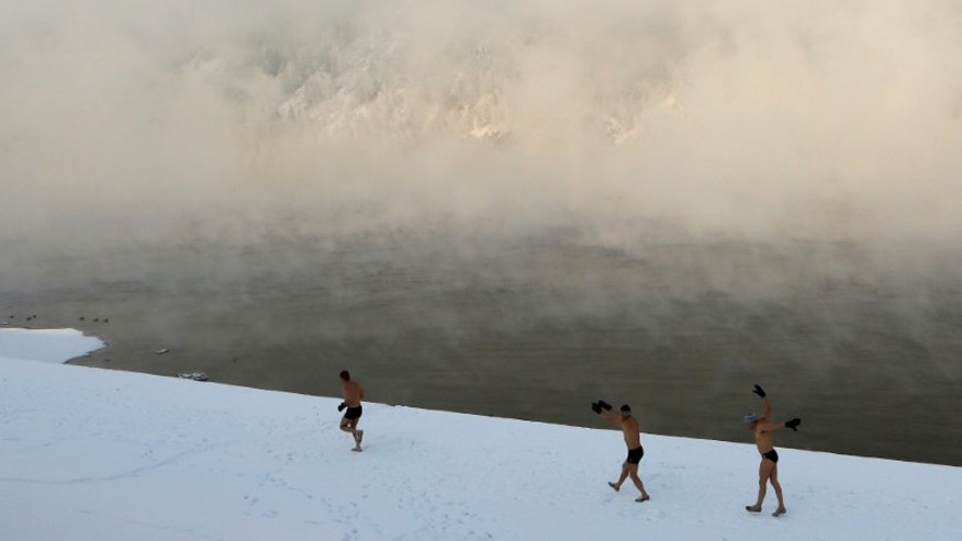 Enthusiasts of winter swimming warm up before their weekly bathing session in Divnogorsk
