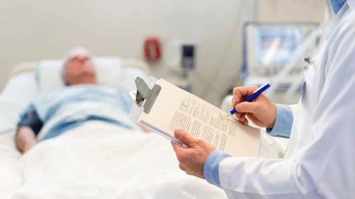 Doctor checking on a senior patient at the ER close-up on a clipboard