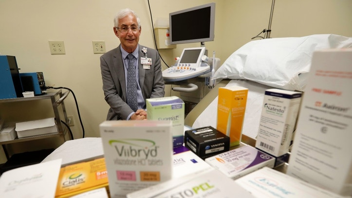 """In this Tuesday, Nov. 29, 2016 photo, Dr. Irwin Goldstein poses in his office in San Diego behind a display of medicine for impotence and for sexual problems. For couples who can't afford the soaring prices for the prescriptions, some take a big risk, buying """"herbal Viagra"""" at gas stations or ordering Viagra online from """"Canadian pharmacies"""" that likely sell counterfeit drugs made in poor countries, says Goldstein, director of San Diego Sexual Medicine. (AP Photo/Gregory Bull)"""