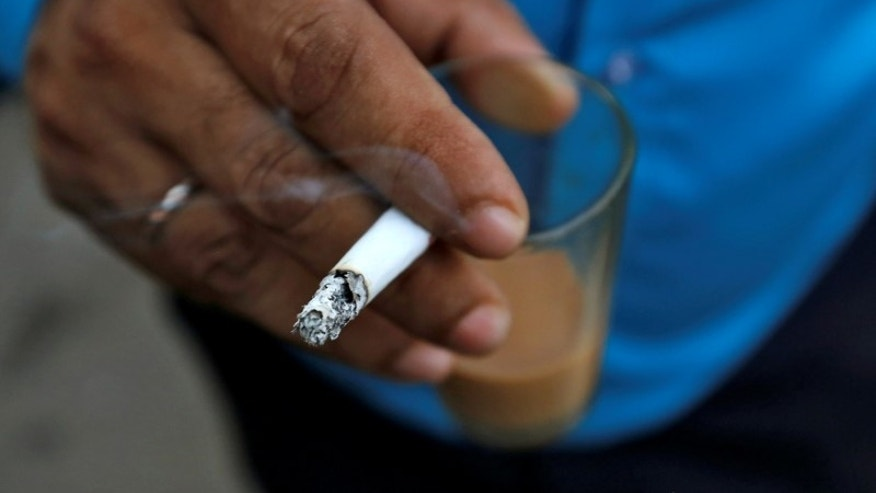 A man smokes a cigarette along a road in Mumbai