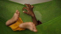 A two-year-old malnourished boy sleeps in a hammock while taking refuge with his family in a classroom in Sukkar
