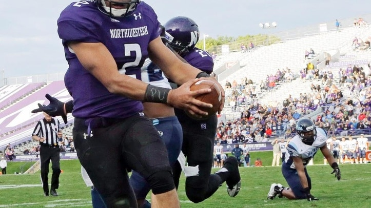 """FILE - In this Sept. 21, 2013 file photo, Northwestern quarterback Kain Colter (2), wears APU for """"All Players United"""" on wrist tape as he scores a touchdown during an NCAA college football game against Maine in Evanston, Ill. The decision to allow Northwestern football players to unionize raises an array of questions for college sports. Among them, state schools vs. public schools, powerhouse programs vs. smaller colleges.  (AP Photo/Nam Y. Huh, File)"""