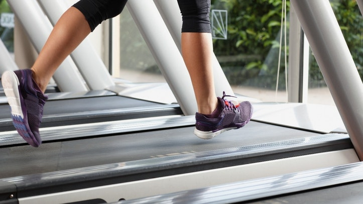 Close-up of woman's legs on treadmill. Some blurred parts due to movement.