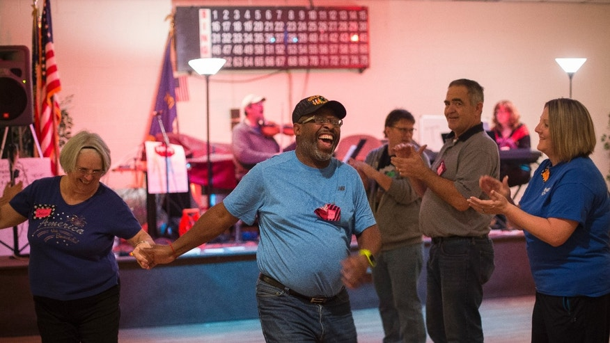 In this Tuesday, Nov. 29, 2016 photo, U.S. Army veteran Roosevelt Smith III, center, enjoys time with other veterans and volunteers in an evening of community dance designed for veterans and families who are affected by PTSD, in Louisville, Ky. The environment is built for maximum comfort: lights are kept low for dancers with traumatic brain injuries, the music is cheery without heavy beats and the location is not advertised to provide anxious visitors a sense of security and privacy. The group sessions are kept small, usually less than 30 people (AP Photo/ David Stephenson)