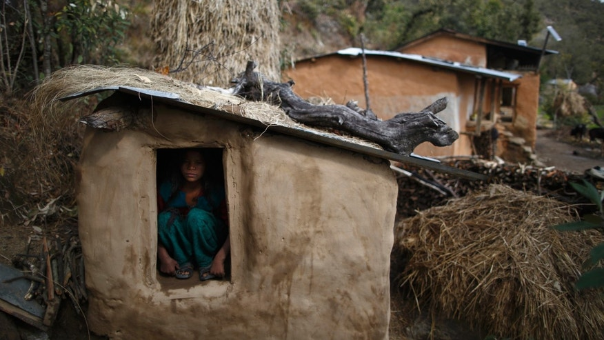 Uttara Saud, 14, sits inside a Chaupadi shed in the hills of Legudsen village in Achham District in western Nepal February 16, 2014
