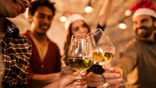 Close up of group of business people toasting with wine during a Christmas party. Focus is on foreground.