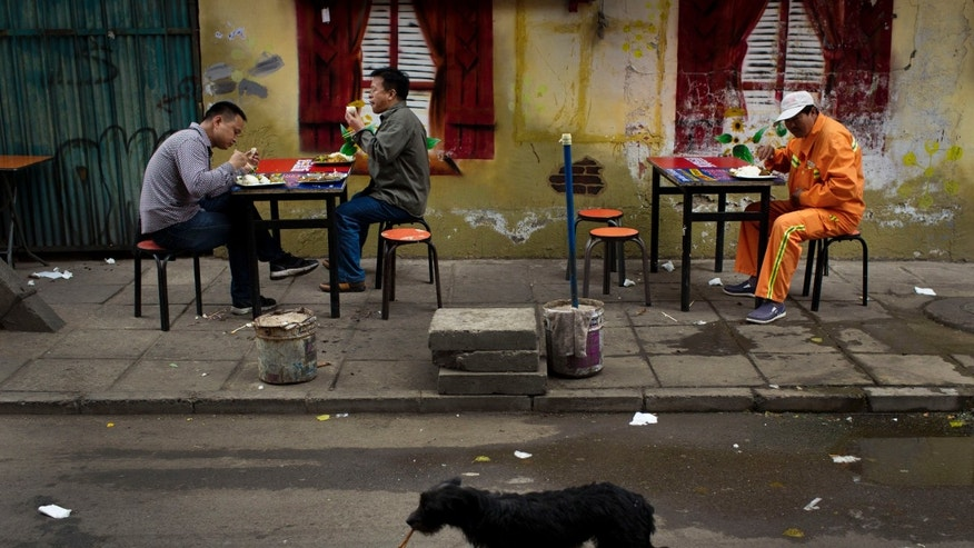 May 9, 2014: Men eat their lunches at a roadside food stall as a dog walks past with a leftover bone in mouth in Beijing.