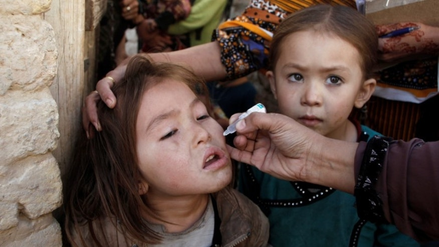 A girl receives polio vaccine drops from anti-polio vaccination worker outside her family home in Quetta