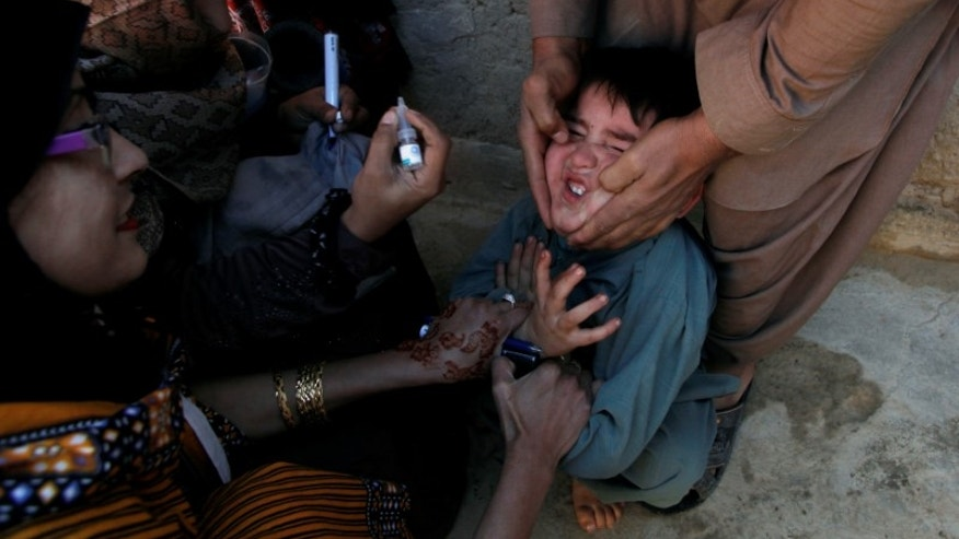 A boy reacts as he is being administered polio vaccine drops by anti-polio vaccination workers along a street in Quetta