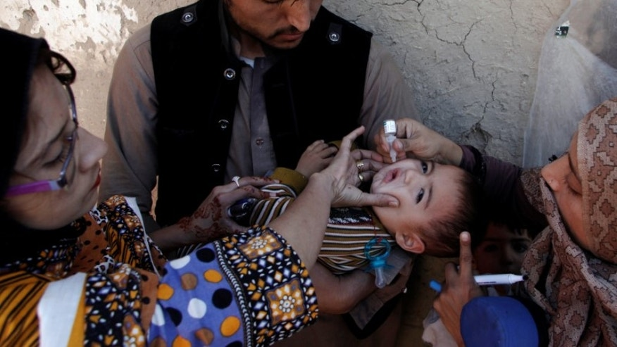 A boy receives polio vaccine drops by anti-polio vaccination workers along a street in Quetta