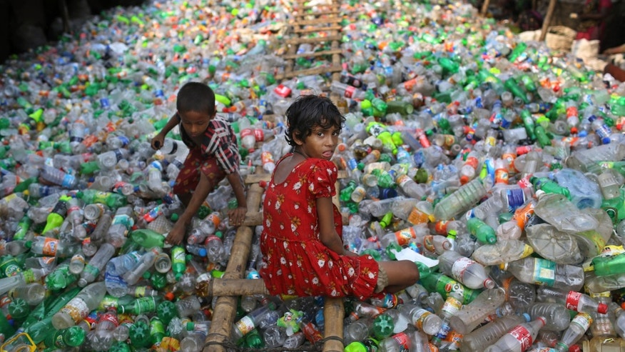 June 12, 2014: Bangladeshi girl Sharmin, 13, looks into the camera as she works at a plastic recycling factory.