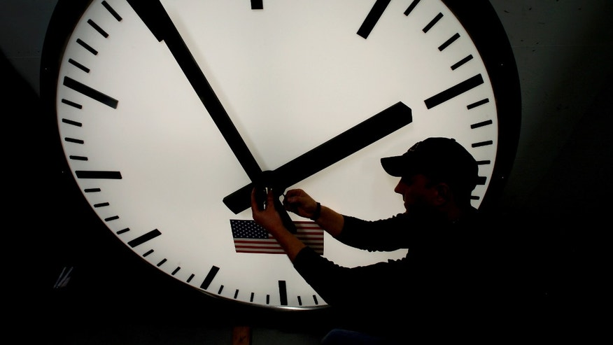 March 7, 2013: Dave LeMote uses an allen wrench to adjust hands on a stainless steel tower clock at Electric Time Company, Inc. in Medfield, Mass.