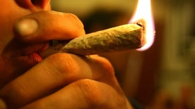 Marihuana joint on fire, in the lips