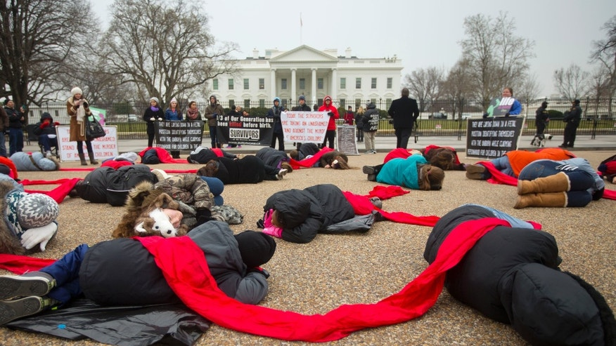 FILE - In a Wednesday, Jan. 21, 2015, file photo, anti-abortion rights activists are connected with a red piece of cloth as they stage a 'die-in' in front of the White House in Washington. Even as the 2016 election outcome intensifies America's abortion debate, a comprehensive new survey released Tuesday, Jan. 17, 2017 by the Guttmacher Institute finds the annual number of abortions in the U.S has dropped to well under 1 million, the lowest level since 1974. (AP Photo/Pablo Martinez Monsivais, File)