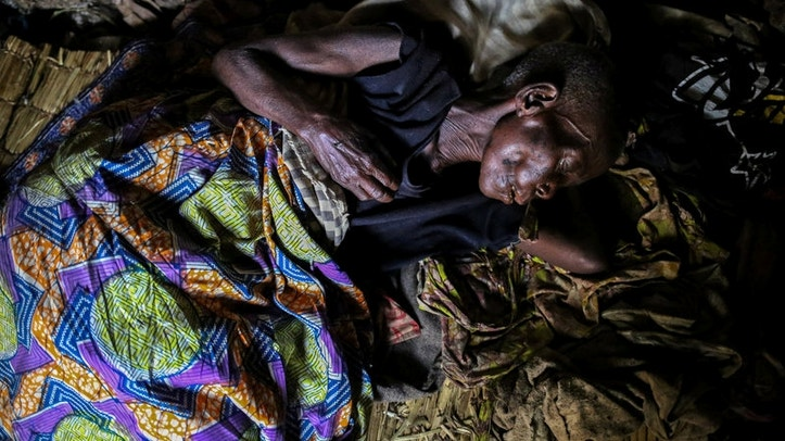FILE PHOTO: A woman, 60, who is suffering from malaria rests in her house at Kagorwa Pygmy camp on Idjwi island in the Democratic Republic of Congo