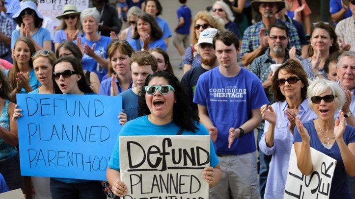 FILE- In this July 28, 2015 file photo, Erica Canaut, center, cheers as she and other anti-abortion activists rally on the steps of the Texas Capitol in Austin, Texas, to condemn the use in medical research of tissue samples obtained from aborted fetuses. Texas is moving forward with booting Planned Parenthood from Medicaid despite federal judges stopping other Republican-controlled states from doing the same. But a string of recent victories for the nation's largest abortion provider will be tested in 2017 under a new president. (AP Photo/Eric Gay, File)