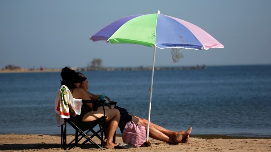 People sit under an umbrella during warm weather at Orchard Beach in the Bronx borough of New York