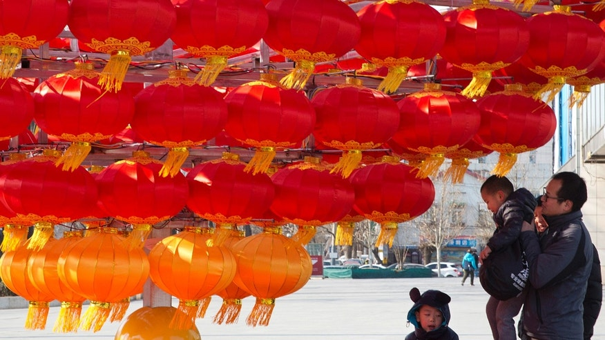 In this photo taken Jan. 23, 2017, a man lifts a child up to lantern decorations setup ahead of the Chinese New Year in Beijing, China. China's National Health and Family Planning Commission said this week that 17.86 million children were born last year, an increase of 1.31 million from 2015. Nearly half of the children born were to couples who already had a child, the commission said. (AP Photo/Ng Han Guan)
